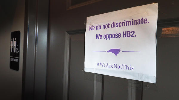 "A unisex sign and the ""We Are Not This"" slogan are outside a bathroom at Bull McCabe's Irish Pub on May 10 in Durham, N.C."