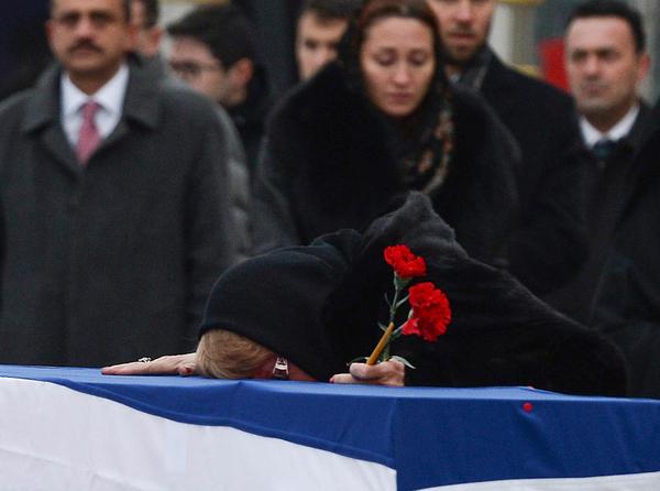 Marina Karlov, the wife of slain Russian Ambassador to Turkey Andrei Karlov, lays her head on his coffin during a ceremony at Esenboga International Airport on Tuesday in Ankara, Turkey.