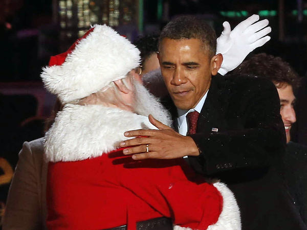 President Obama hugs Santa — and maybe braces for a kiss on the cheek — at the National Christmas Tree lighting ceremony in 2013.