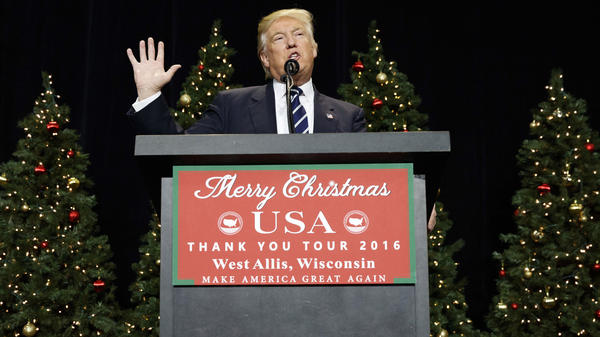 "President-elect Trump, flanked by decorated Christmas trees, speaks at rally in Wisconsin. Trump said at the event, ""We are going to say Merry Christmas again,"" implying a war on Christmas."