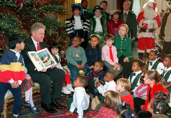"President Clinton reads <em>""Twas the Night Before Christmas</em> to children at the White House in 1995, as Santa looks on."