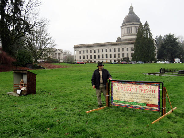 Darrell Barker of the Freedom From Religion Foundation poses with the banner he installed on Friday near a privately-sponsored Nativity scene on the Washington State Capitol Campus.