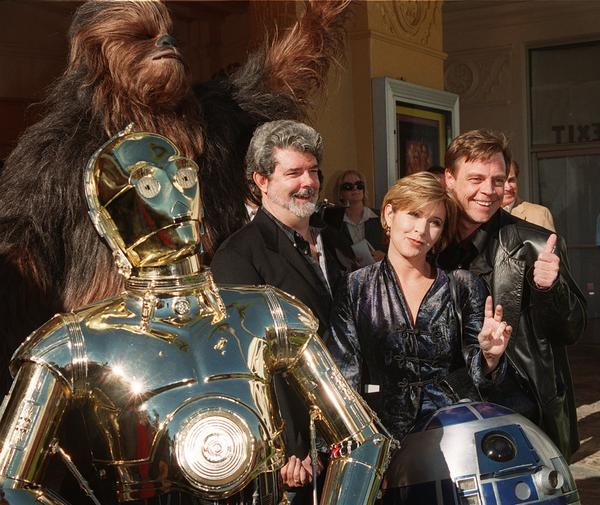 Characters from <em>Star Wars</em> join writer and director George Lucas (center) and actors Carrie Fisher and Mark Hamill at the world premiere of <em>Star Wars Special Edition</em>, in 1997.