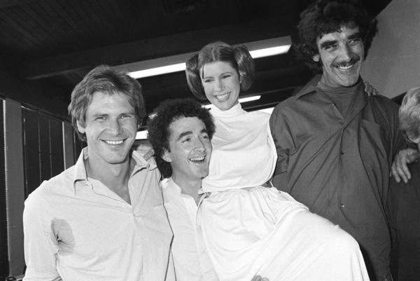 Carrie Fisher (second from right), who played Princess Leia in the movie <em>Star Wars</em>, is pictured with co-stars (left to right) Harrison Ford, who played Han Solo; Anthony Daniels, who played C-3P0; and Peter Mayhew, who played Chewbacca the Wookiee, as they take a break from filming a television special in 1978.