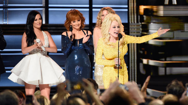 Dolly Parton, pictured with Kacey Musgraves, Reba McEntire and Jennifer Nettles (obscured), accepts the Willie Nelson Lifetime Achievement Award onstage at the CMA Awards in Nashville in November.
