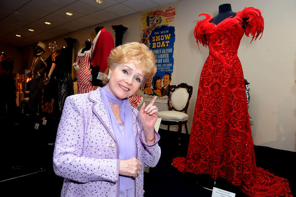 "Debbie Reynolds poses with a costume she wore in <em>The Unsinkable Molly Brown</em> at The Paley Center for Media's Reception for ""Debbie Reynolds: The Exhibit"" in 2011 in Beverly Hills, Calif."
