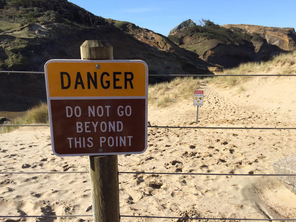 Footprints in the sand behind this fence show how frequently visitors ignore the warning signs at Cape Kiwanda.