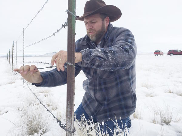 Ammon Bundy, one of the leaders of the Malheur National Wildlife Refuge occupation, winds back barbed-wire fencing after his crew cut an 80-foot gap between federal and private ground Monday in east Oregon.