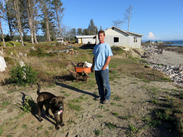 Homeowner Tom Burchard - with his dog Bo - has an air of resignation about soon losing the waterfront property that he said he picked up cheap.