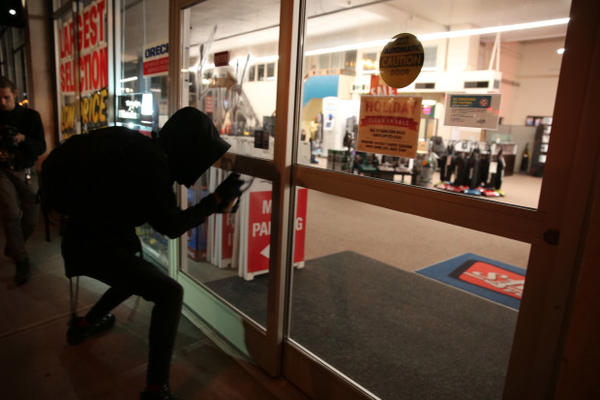 <p>A protester spray paints a storefront during a third night of post-election demonstrations in Portland on Nov. 10, 2016.</p>