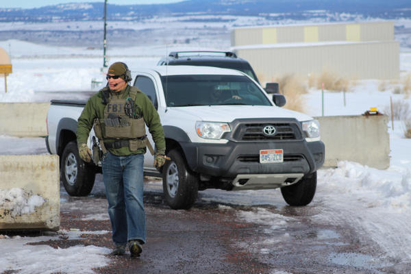 <p>An FBI guard guides a truck out of the compound near the Burns Airport.</p>