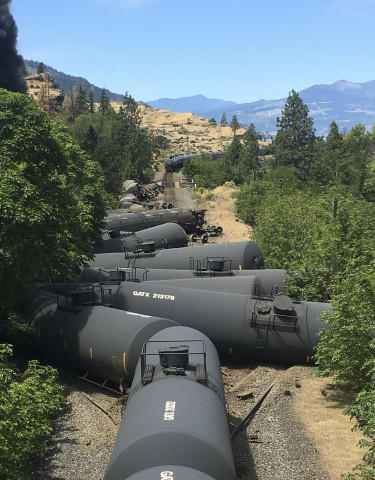 <p>In this photo provided by Silas Bleakley, tank cars, carrying oil, are derailed Friday, June 3, 2016, near Mosier, Ore. The accident happened just after noon about 70 miles east of Portland. It involved numerous cars filled with oil, and one was burning. Highway 84 was closed for a 23-mile stretch between The Dalles and Mosier and the radius for evacuations was a half-mile.</p>