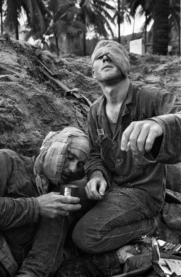 Medic Thomas Cole of Richmond, Virginia, looks up with his one unbandaged eye as he continues to treat wounded S.Sgt. Harrison Pell of Hazleton, Pennsylvania, during a firefight, January 30, 1966. The men belonged to the 1st Cavalry Division, which was engaged in a battle at An Thi, in the Central Highlands, against combined Viet Cong and North Vietnamese forces. This photo appeared on the cover of Life magazine, February 11, 1966, and photographer Henri Huet's coverage of An Thi received the Robert Capa Gold Medal from the Overseas Press Club. (Henri Huet/AP)