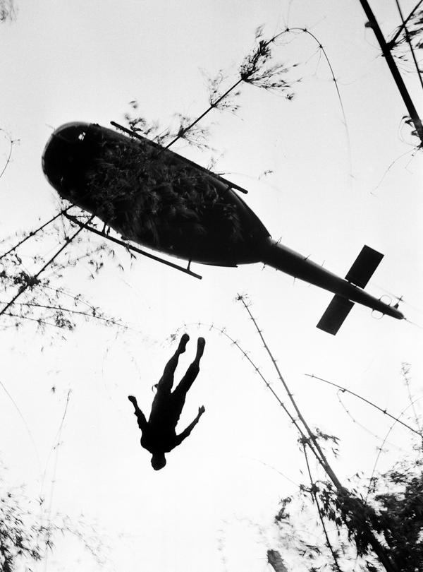The body of a U.S. paratrooper killed in action in the jungle near the Cambodian border is lifted up to an evacuation helicopter in War Zone C, May 14, 1966. The zone, encompassing the city of Tay Ninh and the surrounding area north of Saigon, was the site of the Viet Cong's headquarters in South Vietnam. (Henri Huet/AP)