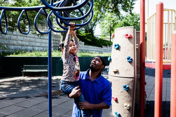 "Shakir Everett helps his niece, Janai Williams, 2, across the monkey bars at Mildred Helms Park in Newark. The playground is an asset in the daytime, but a ""terror zone"" at night, with drug and gang activity, neighbors say."