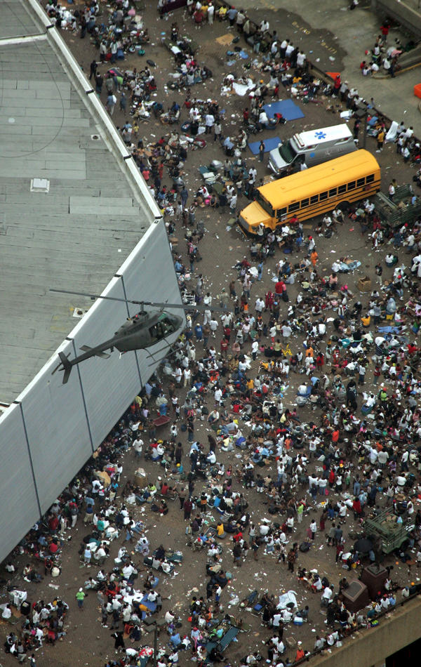 A helicopter flies over residents waiting to be evacuated from the Superdome three days after Katrina hit the city. Regina and Talitha Halley were stranded at the Superdome for seven days.