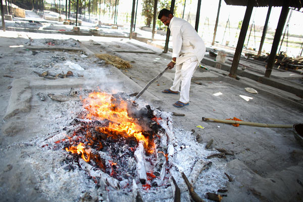 A traditional wood cremation fire is tended by a worker in New Delhi.
