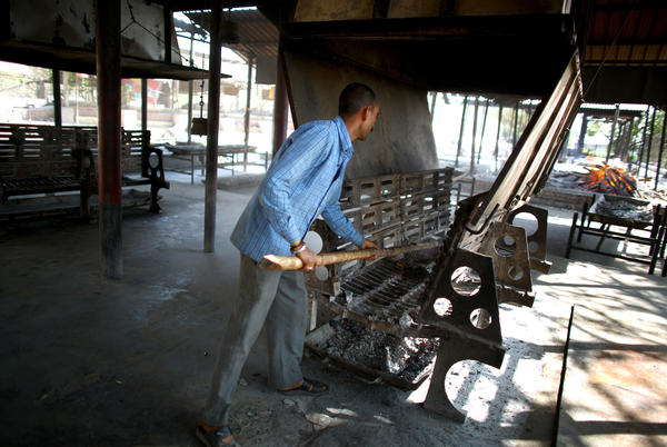 """Braj Kishore Pandey, a crematorium operator, pushes ashes into a pan after a body was burned in a """"green"""" cremations hearth."""