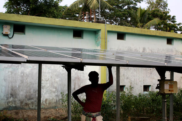 A man stands beneath solar panels that help bring electricity to the village of Rajat Jubilee.