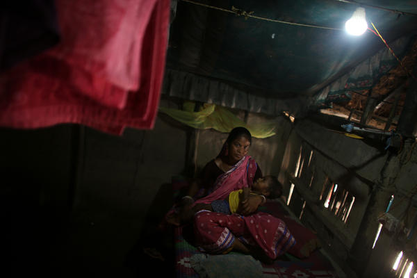 Arati Sardar sits in her house with baby Sridoy. One of the family's goats was taken and eaten by a tiger, but having electricity now helps keep the home safer.