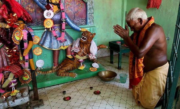 Forest guard Bhabotaron Paik prays in a shrine to the goddess Bonbibi.