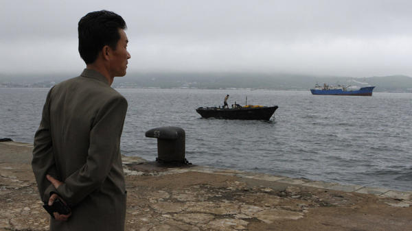 Kim Chol Ho, deputy manager of the Rajin port, in North Korea's Rason Special Economic Zone, looks out at small fishing boats. Despite stepped-up international sanctions, North Korea is still trading extensively with China.