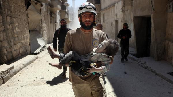 A White Helmets volunteer in Aleppo carries an injured child after an airstrike.