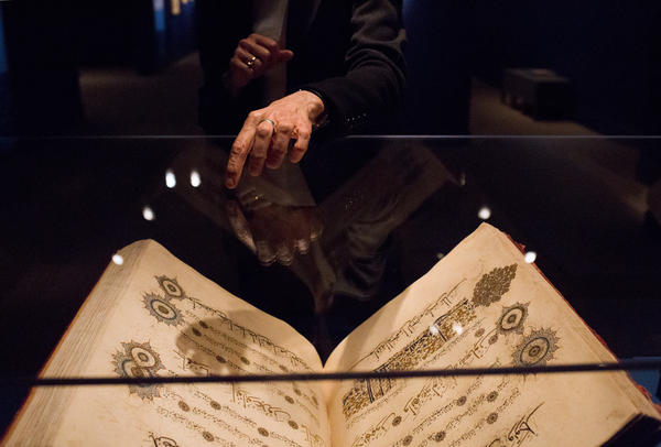 "Massumeh Farhad points to one of the Qurans in the exhibition. As curator, she flipped through all of the books on display. ""Every page is absolutely breathtaking,"" she says."