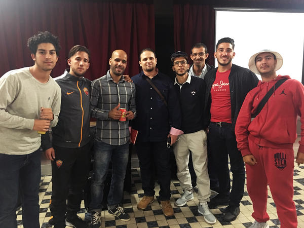 Mourad Benchellali (center, in all black) stands with teenagers after a talk about how to avoid being lured into a radical Islamist group. Standing to Benchellali's right is social worker Hamad Ouanoufi, who works with high-risk youths.