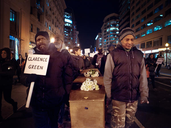 Vigil attendees march down 14th Street NW in Washington, D.C., carrying a casket memorializing the homeless who died this year