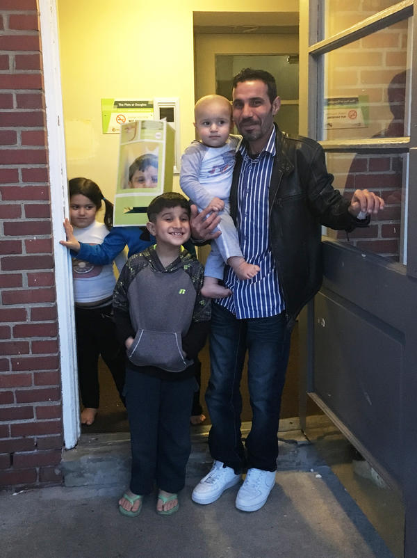 Omar Al-Awad stands with his four children in their apartment complex in Toledo.