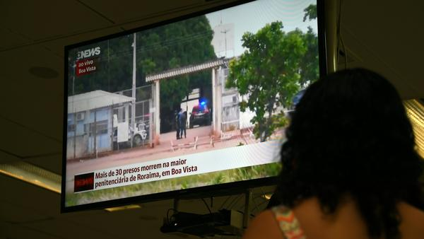 A woman watches a TV news report about the riot early Friday at a prison in Roraima, northern Brazil.