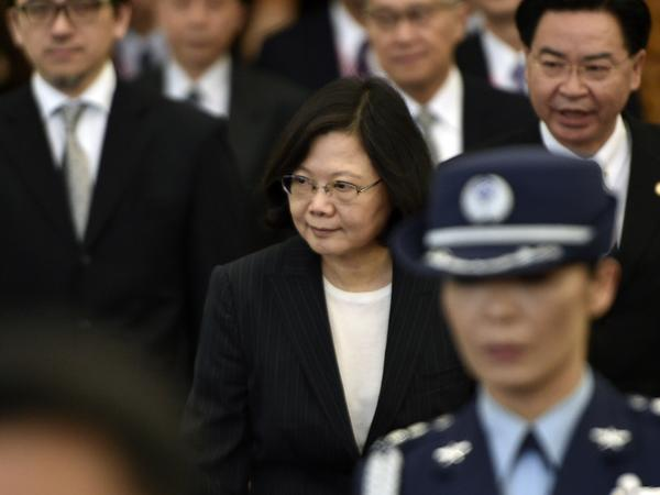 Taiwan President Tsai Ing-wen, center, is escorted by security staff before departing from Taoyuan airport on Saturday. Tsai Ing-wen left for the United States on her way to Central America, a trip that will be closely watched by Beijing.