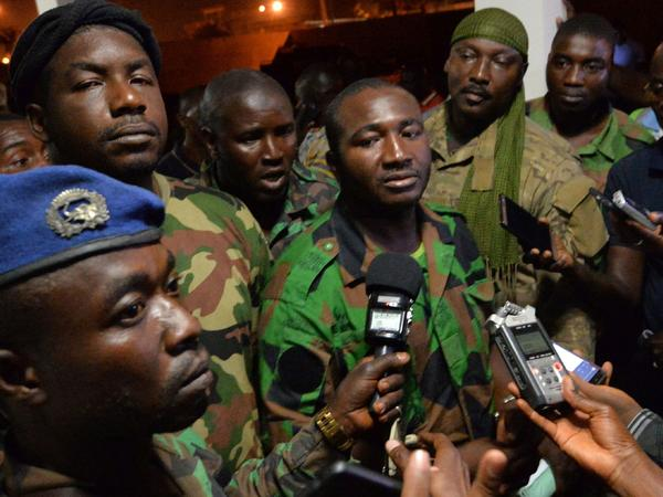 Issiaka Ouattara, center, spokesperson for the mutinous soldiers, speaks to journalists after the announcement of a deal with the Ivory Coast government.