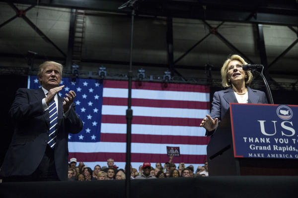 President-elect Donald Trump, left, applauds as his pick for Education Secretary Betsy DeVos, right, speaks during a rally at DeltaPlex Arena, Friday, Dec. 9, 2016, in Grand Rapids, Mich. (Andrew Harnik/AP)