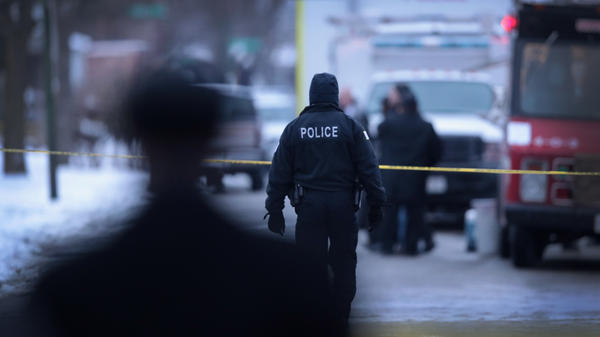 Police investigate the scene of a quadruple homicide in Chicago on Dec. 17.