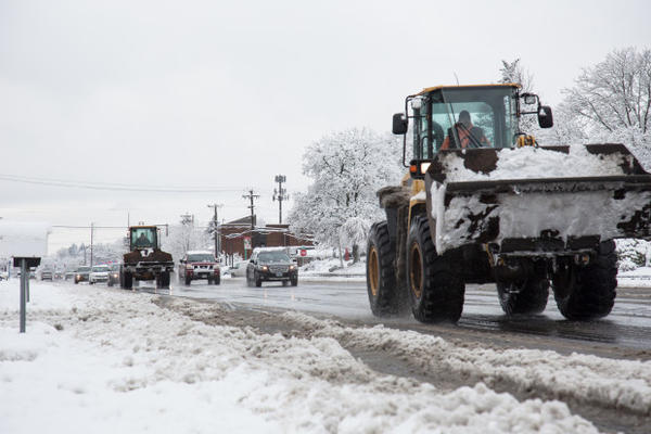 <p>Snow removal trucks drive down Highway 99 in Milwaukie carrying buckets full of snow, Jan. 11, 2017.</p>