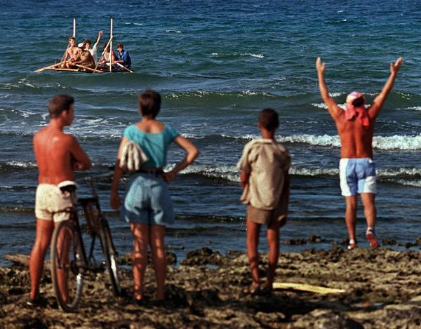 Cubans wave goodbye to rafters headed across the Florida Straits.