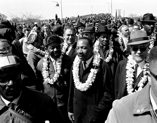 The nonviolent actions of Dr. King inspired young Kennedy Odede. In this March 21, 1965 file photo, King leads a civil rights march across the Edmund Pettus Bridge in Selma, Ala., to protest voting laws.