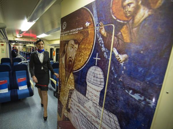 A train stewardess passes through the carriage of the train in Belgrade on Saturday. The interior artwork featured Serbian churches, monasteries and medieval towns, while stewards were clad in Serbian national colors.