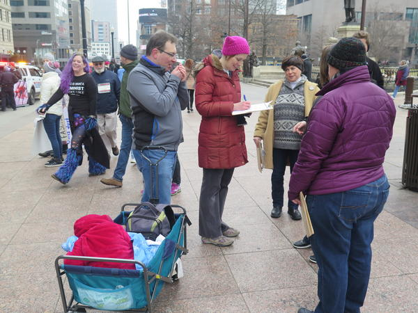 Sarah Hall Phillips (in hat, center) signs a petition at the Women's Sister March.