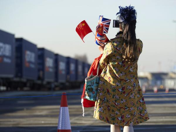 The train's arrival attracted a crowd of onlookers, including this woman who celebrated the new connection with both countries' flags.