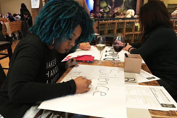 Jewel Cadet makes a protest sign for the Women's March on Washington. She is organizing a free bus ride to the march for transgender, gender nonconforming and homeless protesters from New York City.