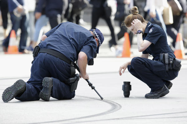 Victoria police officers photograph skid marks at the intersection of Elizabeth and Swanston streets in Melbourne. Authorities said the driver did burnouts with his head leaning out of his sedan's window, before driving into the crowd on Friday.