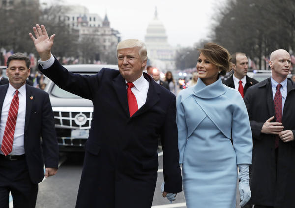 President Trump waves as he walks with first lady Melania Trump during the inauguration parade on Pennsylvania Avenue on Friday.