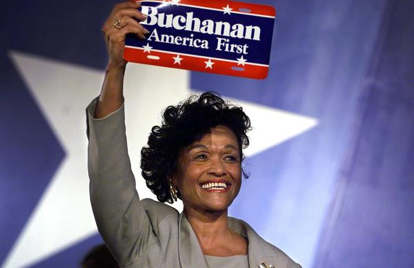 "Reform Party vice presidential candidate Ezola Foster holds up an ""America First"" sign after her nomination acceptance speech in August 2000. Foster, the first African American woman to be nominated for the position, was running on the Reform ticket with presidential candidate Pat Buchanan."