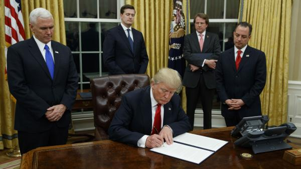 President Donald Trump, flanked by Vice President Mike Pence and Chief of Staff Reince Priebus, signs his first executive order on health care, on Friday.