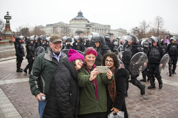 Protesters take a selfie with the police as a backdrop outside the U.S. Capitol during the Women's March on Washington.
