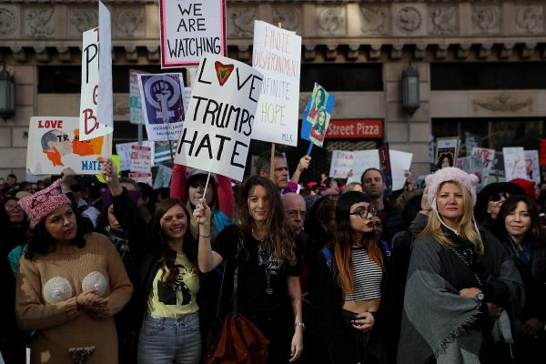 Participants hold signs as they wait for the start of the women's march in Los Angeles.