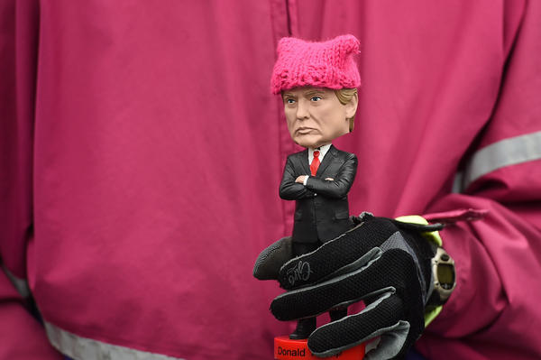 """A protester holds a Donald Trump bobble-head donned with a tiny pink """"pussy hat"""" during Saturday's march in D.C."""